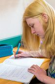 Blonde schoolgirl making homework
