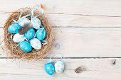 foto of egg whites  - Easter background with blue and white eggs in nest over white wood - JPG