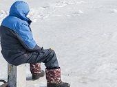 stock photo of ice fishing  - Winter fishing on ice of the frozen sea gulf - JPG