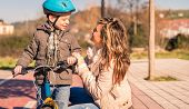 Young woman with child over bicycle on sunny day