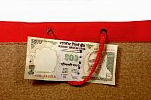 picture of mahatma gandhi  - 500 rupee note in a shopping bag handle - JPG