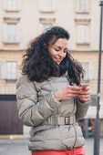 Beautiful Young Brunette Texting In The City Streets