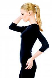picture of slender  - Beautiful slender female model in black fitting clothing posing over white background - JPG