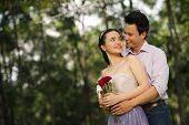 foto of sweethearts  - Happy Vietnamese man embracing his lovely sweetheart - JPG