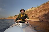 picture of horsetooth reservoir  - mature adult paddler in an expedition decked canoe on calm mountain lake  - JPG