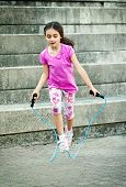 stock photo of skipping rope  - Happy attractive little girl in a trendy pink outfit skipping outdoors using a skipping rope at the bottom of a flight of steps - JPG