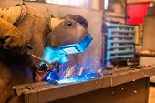 foto of protective eyewear  - Young man with protective mask welding in a factory - JPG