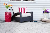 image of spring break  - Single armchair with a red ceramic pedestal table and vase of spring tulips with a matching striped red and white cushion on a brick paved outdoor patio for a relaxing break - JPG