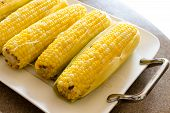 stock photo of corn cob close-up  - Row of delicious boiled fresh corn cobs for a healthy snack served with butter on a platter close up view - JPG