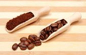 stock photo of coffee grounds  - Coffee beans and ground coffee on wooden spoon coffee grains on wooden background - JPG