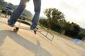 image of skateboard  - skateboarder legs riding on skateboard at skatepark ramp - JPG