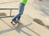 stock photo of skateboard  - skateboarder legs riding on  skateboard at skatepark ramp - JPG