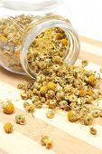 pic of chamomile  - Closeup of dried chamomile dried chamomile pouring out of glass jar on wooden cutting board - JPG