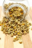foto of chamomile  - Closeup of dried chamomile dried chamomile pouring out of glass jar on wooden cutting board - JPG