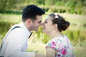 stock photo of suspenders  - Young couple in love looking at each other in the eyes in summer park - JPG