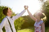 image of suspenders  - Couple in love making a heart shape with their hands in summer sunshine - JPG