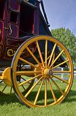 stock photo of stagecoach  - A beautiful yellow painted wooden wheel of a stagecoach glistens in the sun - JPG