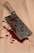 pic of slaughterhouse  - Old rusty meat cleaver with blood on a wooden floor - JPG