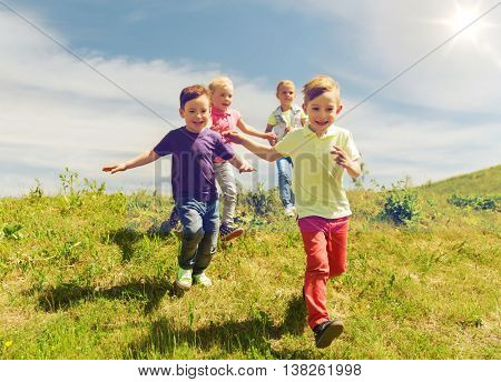 summer, childhood, leisure and people concept - group of happy kids playing tag game and running on