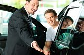 Man buying a car in dealership sitting in his new auto, the salesman talking to him and explaining d