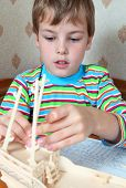 Zealous blonde boy in striped shirt make homemade wooden boat