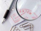 Pen And Stumped Envelope Under Magnifier