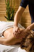 stock photo of massage therapy  - woman in a day spa getting a neck massage - JPG