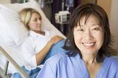 Doctor Standing In Patients Room,Smiling