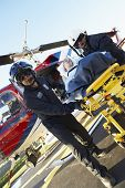stock photo of medevac  - Paramedics unloading patient from Medevac - JPG