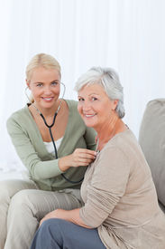 stock photo of health-care  - Nurse taking the heartbreat of her patient at home - JPG