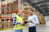 wholesale, logistic business and people concept - warehouse worker and businessman with clipboard an poster