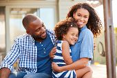 Black family embracing outdoors smiling to camera outside poster