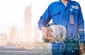 Technician Stand Hand Holding Safety Helmet With Blue Uniform On Petrochemical Industrial Background poster