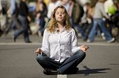 foto of stress relief  - woman meditating yoga in lotus position on busy urban street - JPG