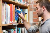 Male student picking a book in a library