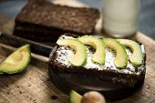 closeup of a slice of rye bread topped with some slices of avocado, and a glass jar of yoghurt, on a poster