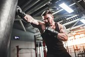 Bearded Male Boxer Training With Punching Bag In Dark Sports Hall. Young Tattoed Boxer Training On P poster