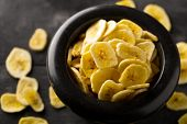 Heap Of Dried Banana Chips Snack In Black Bowl On Dark Rustic Table With Selective Focus poster