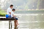stock photo of rod  - Man and boy fishing on the lake - JPG