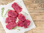 Pieces Of Raw Meat. Raw Beef With Spices And Thyme On White Parchment Paper On Wooden Rough Rustic B poster