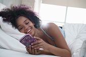 Young African American Woman In Bed At Home. Happy Black Girl Smiling While Texting Message On Mobil poster