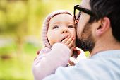 An Unrecognizable Father With His Toddler Daughter Outside In Green Sunny Spring Nature., Kissing. poster