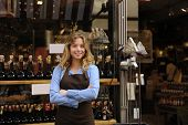 stock photo of liquor bottle  - small business owner in front of store - JPG