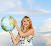 Blonde In Field On Green Grass Holding Globe In Hand Under Blue Sky(Heaven)