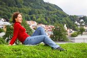 stock photo of jupe  - Woman lies on grass at background of Bergen town among trees under mountain - JPG