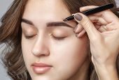 Make-up Artist Plucks Eyebrows With Tweezers To A Woman With Curly Brown Hair And Nude Make-up. Beau poster