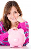 Woman saving money in a piggybank - isolated over a white background