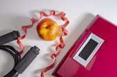 Losing Weight Concept. Weight Scale With A Jump Rope, Red Measuring Tape And An Apple poster