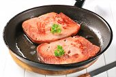 Two slices of luncheon meat on a hot black pan