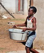 African child portrait in a village in the rural  Botswana carry heavy container with water , in fro poster